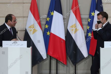 French President Emmanuel Macron, right, adjusts his mask as Egyptian President Abdel-Fattah el-Sissi looks after a joint press conference at the Elysee palace, in Paris. Egyptian President Abdel-Fattah el-Sissi was meeting Monday with French President Emmanuel Macron for talks on fighting terrorism, the conflict in Libya and other regional issues as part of a state visit to France, amid criticism from human rights groups over the Egyptian leader's crackdown on dissent