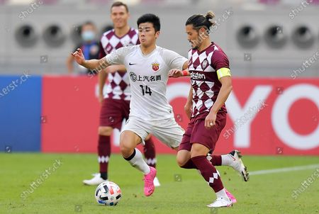 Hotaru Yamaguchi (R) of Vissel in action against Li Shenglong of SIPG during the AFC Champions League Round of 16 match between Vissel Kobe and Shanghai SIPG FC at the Khalifa International Stadium in Doha, Qatar, 07 December 2020.