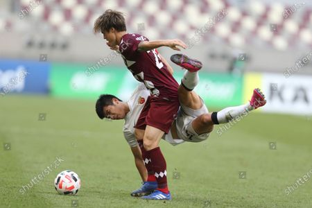 Shanghai SIPG's Li Shenglong and Vissel Kobe's Gotoku Sakai, top, fight for the ball during a round of 16 AFC Champions League match in Doha, Qatar