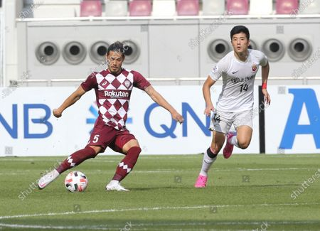 Vissel Kobe's Hotaru Yamaguchi in action in front of Shanghai SIPG's Li Shenglong during a round of 16 AFC Champions League match in Doha, Qatar
