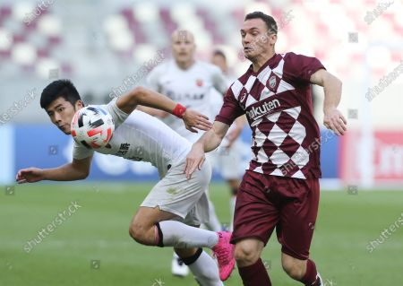 Shanghai SIPG's Li Shenglong, left, and Vissel Kobe's Thomas Vermaelen fight for the ball during a round of 16 AFC Champions League match in Doha, Qatar