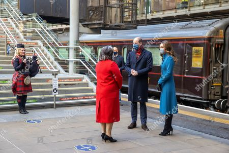 Prince William and Catherine Duchess of Cambridge are met by Deputy Lord Lieutenant Sandra Cumming (second left) and piper Louise Marshall (left) as they arrive by train at Edinburgh Waverley Station on the second day of a three-day tour across the country