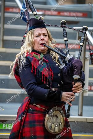 Piper Louise Marshall awaits the arrival of the Duke and Duchess of Cambridge at Edinburgh Waverley Station on the second day of a three-day tour across the country