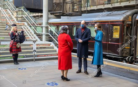 Stock Image of Prince William and Catherine Duchess of Cambridge are met by Deputy Lord Lieutenant Sandra Cumming (second left) and piper Louise Marshall (left) as they arrive by train at Edinburgh Waverley Station on the second day of a three-day tour across the country