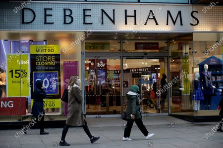 People wearing face masks walk past the Debenhams department store, which is in the process of being closed down, on Oxford Street, in London, . Frasers Group, the British department store chain run by billionaire Mike Ashley, says it is in negotiations about a potential rescue of Debenhams that could safeguard some of the 12,000 jobs at risk