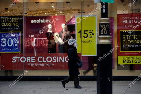 Woman wearing a face shield and face mask to curb the spread of coronavirus walks past the Debenhams department store, which is in the process of being closed down, on Oxford Street, in London, . Frasers Group, the British department store chain run by billionaire Mike Ashley, says it is in negotiations about a potential rescue of Debenhams that could safeguard some of the 12,000 jobs at risk