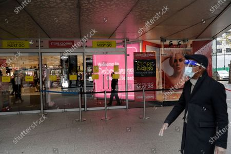 Man wearing a face shield, face mask and disposable gloves to curb the spread of coronavirus walks past the Debenhams department store, which is in the process of being closed down, on Oxford Street, in London, . Frasers Group, the British department store chain run by billionaire Mike Ashley, says it is in negotiations about a potential rescue of Debenhams that could safeguard some of the 12,000 jobs at risk