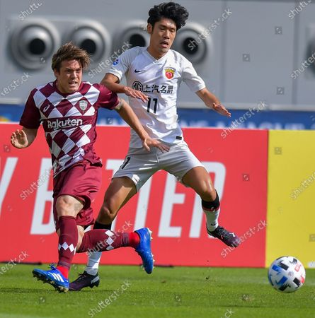Lyu Wenjun (R) of Shanghai SIPG FC vies with Gotoku Sakai of Vissel Kobe during the round 16 match of the AFC Champions League between Shanghai SIPG FC of China and Vissel Kobe of Japan in Doha, Qatar, Dec. 7, 2020.