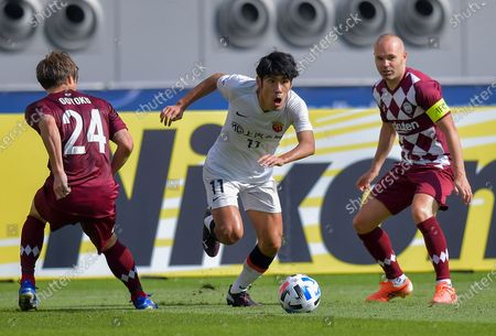 Lyu Wenjun (C) of Shanghai SIPG FC vies with Andres Iniesta (R) and Gotoku Sakai of Vissel Kobe during the round of 16 match of the AFC Champions League between Shanghai SIPG FC of China and Vissel Kobe of Japan in Doha, Qatar, Dec. 7, 2020.