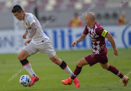 Yu Rui (L) of Shanghai SIPG FC vies with Andres Iniesta of Vissel Kobe during the round of 16 match of the AFC Champions League between Shanghai SIPG FC of China and Vissel Kobe of Japan in Doha, Qatar, Dec. 7, 2020.