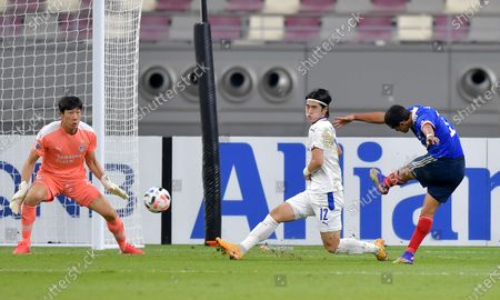 Erik (R) of Marinos takes a shot on goal against Kim Tae-Hwan (C) and goalkeeper Yang Hyung-Mo of Bluewings during the AFC Champions League Round of 16 match between the Yokohama F. Marinos and the Suwon Samsung Bluewings at the Khalifa International Stadium in Doha, Qatar, 07 December 2020.