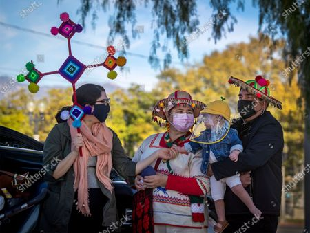 Wearing masks and traditional hats, dress and decorated cross from their native homeland in Mexico, Lia Cervantes, left, of Whittier, and her parents Francisca Lerma and Nahut Cervantes, of San Gabriel, share a moment with her son and grandson, Oliver Renteria, 18 months-old, during mass for the annual Procession and Mass in honor of Our Lady of Guadalupe at the parking lot of the San Gabriel Mission on Sunday, Dec. 6, 2020 in San Gabriel, CA. Oliver has Down Syndrome and a congenital heart defect and the family prayed that his heart surgery would be successful and return to the the Our Lady of Guadalupe mass this year to celebrate and give thanks to God. The annual Archdiocese of Los Angeles procession and mass, presided by Archbishop Jose H. Gomez, has been taking place since 1931 in East Los Angeles but this year was held in San Gabriel, beginning at Vincent Lugo Park and proceeding to the San Gabriel Mission. The car procession was followed by a mass afterward at the mission parking lot, where only 100 people were allowed to attend (and live streamed for the rest), The parade/procession in normal years has been attended by 10,000 people. The procession and mass is held the first Sunday of December before the Virgen de Guadalupe Feast Day on Dec. 12. The Virgen De Guadalupe is the patron saint of Mexico. (Allen J. Schaben / Los Angeles Times)