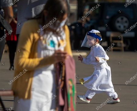 Dressed as a priest and wearing a face shield, Fabian Acuna, 2, right, of East Los Angeles, dances while Maria Quintero, left, of Los Angeles, kneels in prayer during the 89th annual Procession and Mass in honor of Our Lady of Guadalupe at the parking lot of Mission San Gabriel Arcangel, with burned roof in background, on Sunday, Dec. 6, 2020 in San Gabriel, CA. The procession and Mass are the culmination of a three-month pilgrimage of the exact digital image of the Lady of Guadalupe. The annual Archdiocese of Los Angeles procession and mass, presided by Archbishop Jose H. Gomez, has been taking place since 1931 in East Los Angeles but this year was held in San Gabriel, beginning at Vincent Lugo Park and proceeding to the San Gabriel Mission. The car procession was followed by a mass afterward at the mission parking lot, where only 100 people were allowed to attend (and live streamed for the rest), The parade/procession in normal years has been attended by 10,000 people. The procession and mass is held the first Sunday of December before the Virgen de Guadalupe Feast Day on Dec. 12. The Virgen De Guadalupe is the patron saint of Mexico. (Allen J. Schaben / Los Angeles Times)