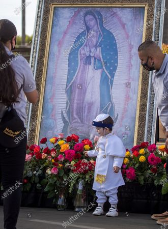 Dressed as a priest and wearing a face shield, Fabian Acuna, 2, of East Los Angeles, looks at flowers in front of an image of the the Virgen de Guadalupe during the 89th annual Procession and Mass in honor of Our Lady of Guadalupe at the parking lot of Mission San Gabriel Arcangel, with burned roof in background, on Sunday, Dec. 6, 2020 in San Gabriel, CA. The procession and Mass are the culmination of a three-month pilgrimage of the exact digital image of the Lady of Guadalupe. The annual Archdiocese of Los Angeles procession and mass, presided by Archbishop Jose H. Gomez, has been taking place since 1931 in East Los Angeles but this year was held in San Gabriel, beginning at Vincent Lugo Park and proceeding to the San Gabriel Mission. The car procession was followed by a mass afterward at the mission parking lot, where only 100 people were allowed to attend (and live streamed for the rest), The parade/procession in normal years has been attended by 10,000 people. The procession and mass is held the first Sunday of December before the Virgen de Guadalupe Feast Day on Dec. 12. The Virgen De Guadalupe is the patron saint of Mexico. (Allen J. Schaben / Los Angeles Times)