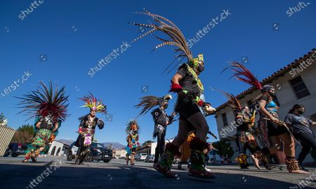 Stock Image of Dancers from Danza Aguilas de Tepeyac lead the 89th annual walking-turned to car Procession and Mass in honor of Our Lady of Guadalupe as they arrive at the parking lot of Mission San Gabriel Arcangel on Sunday, Dec. 6, 2020 in San Gabriel, CA. The procession and Mass are the culmination of a three-month pilgrimage of the exact digital image of the Lady of Guadalupe. The annual Archdiocese of Los Angeles procession and mass, presided by Archbishop Jose H. Gomez, has been taking place since 1931 in East Los Angeles but this year was held in San Gabriel, beginning at Vincent Lugo Park and proceeding to the San Gabriel Mission. The car procession was followed by a mass afterward at the mission parking lot, where only 100 people were allowed to attend (and live streamed for the rest), The parade/procession in normal years has been attended by 10,000 people. The procession and mass is held the first Sunday of December before the Virgen de Guadalupe Feast Day on Dec. 12. The Virgen De Guadalupe is the patron saint of Mexico. (Allen J. Schaben / Los Angeles Times)