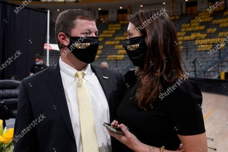 Stock Photo of New Southern Mississippi NCAA college football coach Will Hall confers with wife, Rebecca Hall, after an introductory news conference where he was named the school's 22nd head coach, in Hattiesburg, Miss. Hall served the last two years as offensive coordinator at Tulane