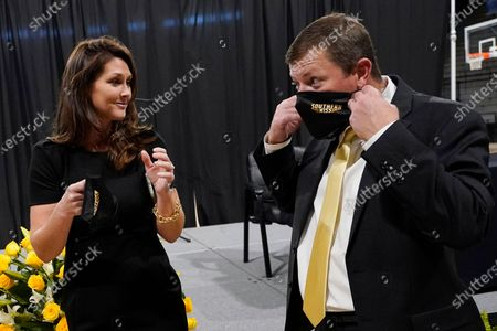 New Southern Mississippi NCAA college football coach Will Hall and wife, Rebecca Hall, put on masks following a quick photo session after the introductory news conference where he was named the school's 22nd head coach, in Hattiesburg, Miss. Hall served the last two years as offensive coordinator at Tulane