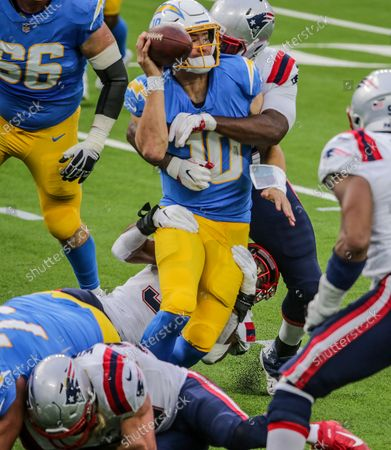 Inglewood, CA, Sunday, December 6, 2020 - Los Angeles Chargers quarterback Justin Herbert (10) manages to throw an incomplete pass as he is harassed by New England Patriots defensive end John Simon (55) and New England Patriots defensive tackle Adam Butler (70) at SoFi Stadium. (Robert Gauthier/ Los Angeles Times)