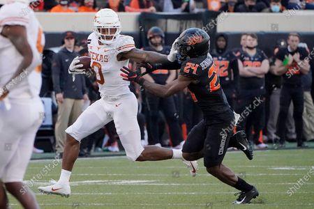 Texas wide receiver Tarik Black (0) is pursued by Oklahoma State cornerback Jarrick Bernard-Converse (24) during an NCAA college football game against Texas in Stillwater, Okla