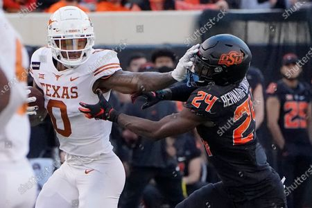 Stock Picture of Texas wide receiver Tarik Black (0) is pursued by Oklahoma State cornerback Jarrick Bernard-Converse (24) during an NCAA college football game against Texas in Stillwater, Okla