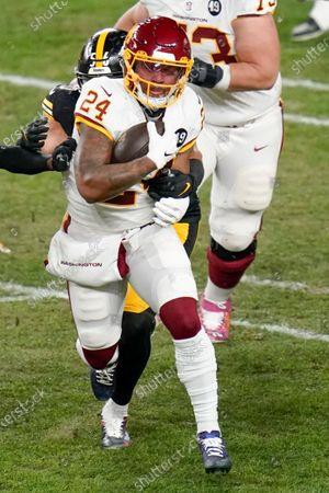 Washington Football Team running back Antonio Gibson (24) runs the ball past Pittsburgh Steelers linebacker Alex Highsmith (56) during an NFL football game, in Pittsburgh