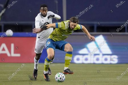 Minnesota United midfielder Kevin Molino, left, and Seattle Sounders midfielder Gustav Svensson vie for the ball during the second half of an MLS playoff Western Conference final soccer match, in Seattle