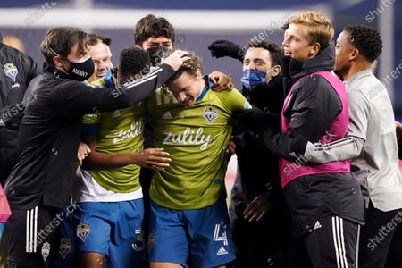 Seattle Sounders' Gustav Svensson (4) is surrounded by teammates after the team beat Minnesota United in an MLS playoff Western Conference final soccer match, in Seattle. Svensson scored the third, and winning goal, for the team as the Sounders won 3-2