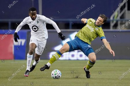 Minnesota United midfielder Kevin Molino (7) and Seattle Sounders midfielder Gustav Svensson vie for the ball during the second half of an MLS playoff Western Conference final soccer match, in Seattle