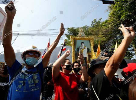 Thai anti-government protesters flash the three-finger salute in front of a portrait of Thai King Maha Vajiralongkorn Bodindradebayavarangkun (C) as they gather to show support to pro-democracy protest leaders who are meeting the police on acknowledge lese majeste charges, at a police station in Nonthaburi province, on the outskirts of Bangkok, Thailand, 08 December 2020. Pro-democracy leaders reported to the police station to hear additional charges under section 112 of the Thai criminal code, for allegedly insulting the monarchy, during the ongoing pro-democracy protests.