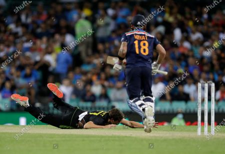 Australia's Sean Abbott, left, falls on the ground in an attempt to field the ball after a shot played by India's captain Virat Kohli, right, during the third T20 international cricket match between Australia and India at the Sydney Cricket Ground in Sydney, Australia