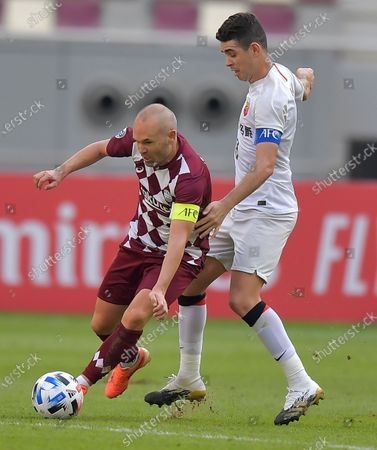 Oscar (R) of Shanghai SIPG FC vies with Andres Iniesta of Vissel Kobe during the round 16 match of the AFC Champions League between Shanghai SIPG FC of China and Vissel Kobe of Japan in Doha, Qatar, Dec. 7, 2020.