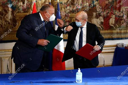 "Egyptian Foreign Minister Sameh Shoukry, left, and French Foreign Minister Jean-Yves le Drian elbow bump during a signing ceremony in Paris, Tuesday, Dec.8, 2020. French President Emmanuel Macron acknowledged Monday ""disagreements"" with Egyptian President Abdel-Fattah el-Sissi over human rights, but said it will not prevent France from reaching economic and defense deals with the North African country, which has seen the heaviest crackdown on dissent in its modern history"