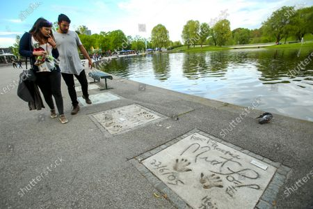 Stock Image of People sightseeing the celebrity handprints in concrete at the Munich Olympic Walk Of Stars in Olympic Park in Munich, Germany.