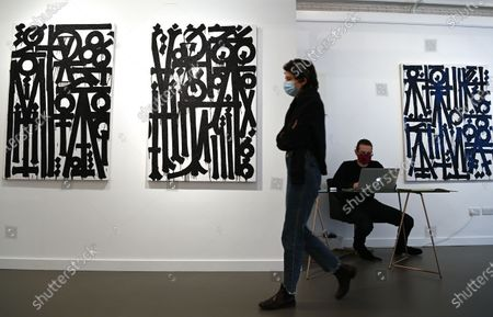 Stock Picture of A gallery employee poses for photographers next to untitled works by US street artist, RETNA (Marquis Lewis) during an exhibition called 'Valle de Guadalupe' in London, Britain 08 December 2020. The exhibition will be held at the HOFA gallery in London from 08 until 31 December 2020.