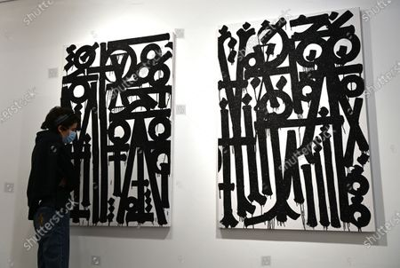 A gallery employee poses for photographers next to untitled works by US street artist, RETNA (Marquis Lewis) during an exhibition called 'Valle de Guadalupe' in London, Britain 08 December 2020. The exhibition will be held at the HOFA gallery in London from 08 until 31 December 2020.