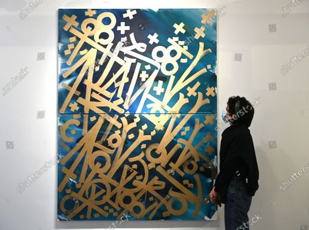 Stock Image of A gallery employee poses for photographers next to untitled works by US street artist, RETNA (Marquis Lewis) during an exhibition called 'Valle de Guadalupe' in London, Britain 08 December 2020. The exhibition will be held at the HOFA gallery in London from 08 until 31 December 2020.