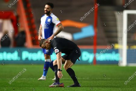Referee Steve Martin picks up the lost boot of Antoine Semenyo of Bristol City and returns it