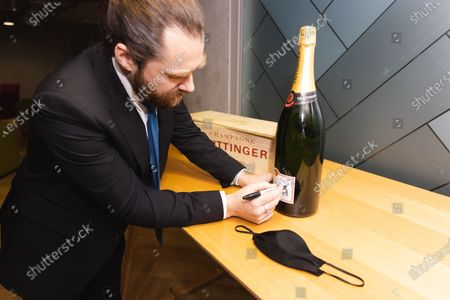 Exclusive - Richard Rankin signing a bottle of Taittinger Champagne