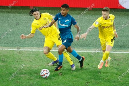 Dortmund's Nico Schulz, left, Marco Reus, right, and Zenit's Wilmar Barrios fight for the ball during the Champions League group F soccer match between Zenit St.Petersburg and Borussia Dortmund at the Saint Petersburg stadium in St. Petersburg, Russia
