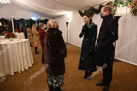 Prince William, (R) and Britain's Catherine, Catherine Duchess of Cambridge (2nd R), wearing protective face coverings to combat the spread of the coronavirus, attend an event to thank local volunteers and key workers for the work they are doing during the coronavirus pandemic and over Christmas in the quadrangle of Windsor Castle in Windsor, west of London, on December 8, 2020 - The Queen and members of the royal family gave thanks to local volunteers and key workers for their work in helping others during the coronavirus pandemic and over Christmas at Windsor Castle in what was also the final stop for the Duke and Catherine Duchess of Cambridge on their tour of England, Wales and Scotland.