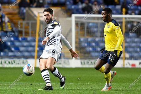 Stock Image of Forest Green Rovers midfielder Dan Sweeney (4) looks to release the ball  under pressure from Oxford United forward (on loan from QPR)  Olamide Shodipo (25) during the EFL Trophy match between Oxford United and Forest Green Rovers at the Kassam Stadium, Oxford