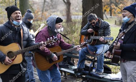 People gather to play Beatles' songs at the memorial to British musician John Lennon in Strawberry Fields as people gather to mark the 40th anniversary of Lennon's death in Central Park in New York, New York, USA, 08 December 2020. Lennon, one of the founding members of The Beatles, was killed in 1980 when he was shot outside of his New York apartment building.