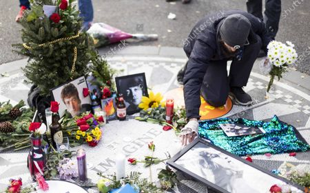 A man places flowers at the permanent memorial to British musician John Lennon in Strawberry Fields as people gather to mark the 40th anniversary of Lennon's death in Central Park in New York, New York, USA, 08 December 2020. Lennon, one of the founding members of The Beatles, was killed in 1980 when he was shot outside of his New York apartment building.