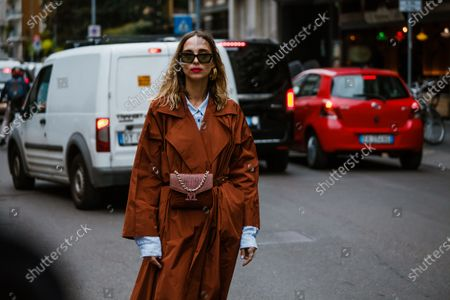 Candela Novembre is seen wearing rusty brown trench coat, belt bag, blue button shirt, seen outside Max Mara show during Milan Fashion Week Womenswear Spring Summer 2020