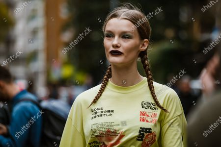 Stock Picture of Model Kris Grikaite wears a lime green shirt with Japanese text, outside Max Mara show during Milan Fashion Week Womenswear Spring Summer 2020
