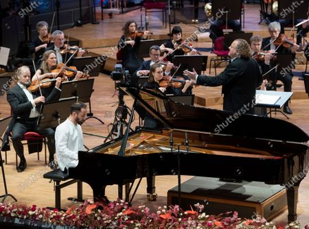 Stock Image of Russian-German pianist Igor Levit (L) and French conductor Stéphane Denève together with the Royal Stockholm Philharmonic Orchestra perform Beethoven's Piano Concerto No. 5 (Emperor Concerto) during the Nobel Prize Concert 2020 at the Stockholm Concert Hall