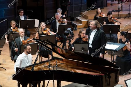 Stock Picture of Russian-German pianist Igor Levit (L) and French conductor Stéphane Denève together with the Royal Stockholm Philharmonic Orchestra perform Beethoven's Piano Concerto No. 5 (Emperor Concerto) during the Nobel Prize Concert 2020 at the Stockholm Concert Hall