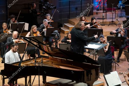 Russian-German pianist Igor Levit (L) and French conductor Stéphane Denève together with the Royal Stockholm Philharmonic Orchestra perform Beethoven's Piano Concerto No. 5 (Emperor Concerto) during the Nobel Prize Concert 2020 at the Stockholm Concert Hall