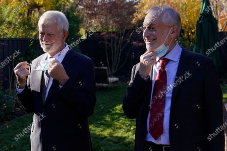 Stock Image of Robert B. Wilson, left, and Paul R. Milgrom take off protective masks to pose for photos before they were presented with the Nobel prize for economics, by Consul General Barbro Osher, Honorary Consulate General of Sweden in San Francisco, at a ceremony in Palo Alto, Calif