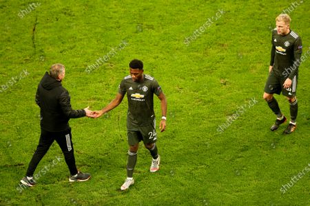 Manchester United's Timothy Fosu-Mensah and manager Ole Gunnar Solskjaer shake hands besides Manchester United's Donny van der Beek, right, after the Champions League group H soccer match between RB Leipzig and Manchester United at the RB Arena in Leipzig, Germany